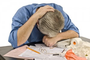 upset man with head down over papers worrying about tax audit